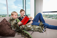 Boy dressed in dinosaur costume reading picture book with father on sofa bed at home
