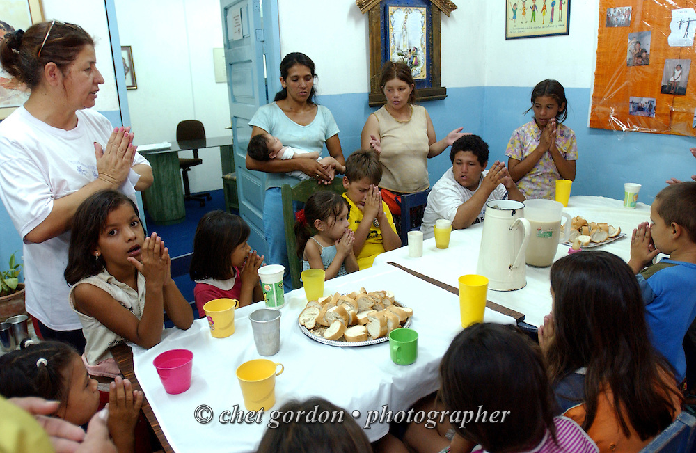 ASUNCION, PARAGUAY.  Young Paraguayan street children, mothers (rear) and a volunteer (left) say a prayer together prior to a meal of bread and powdered milk in the Asociacion Cultural Justicia y Verdad (Association of Cultural Justice and Truth) in Asuncion, Paraguay on Friday evening, March 17, 2006. The shelter founded by Dr. Chantal Hulin, is run out of a renovated auto garage, where volunteers provide showers, administer health care, simple meals, and classroom activities to some of the hundreds of homeless street children that panhandle and clean windshields for money on the neighborhood streets.
