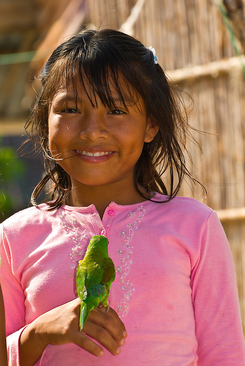 Kuna Indian girl holding a parakeet in her village on Corbisky Island, San Blas Islands (Kuna Yala), Caribbean Sea, Panama