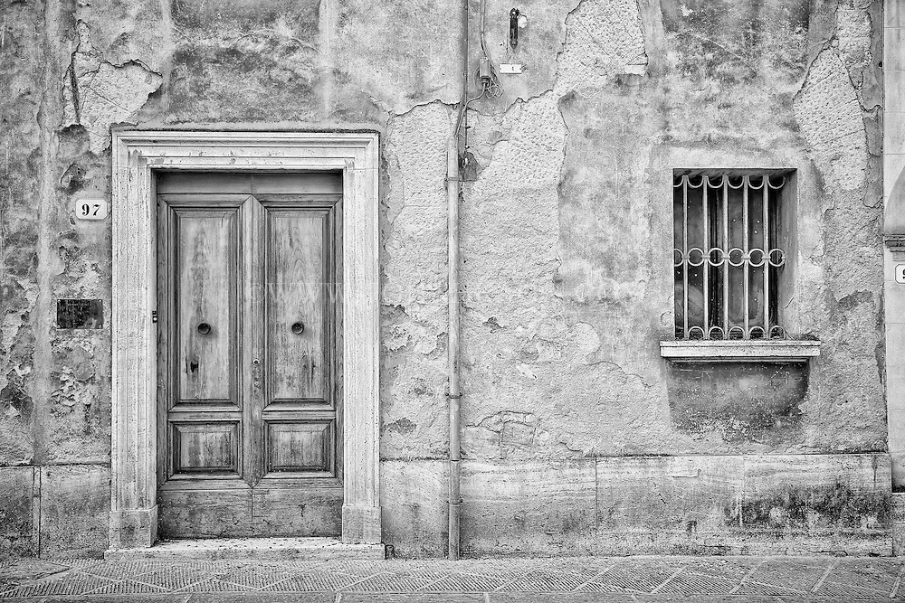 Black and white photo of a rustic Italian residence in San Quirico d'Orcia, Italy.