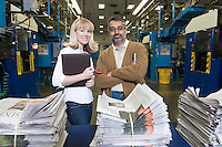 Man and woman working in newspaper factory portrait
