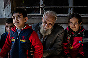 4 February 2019 &ndash; Mosul &ndash; Iraq &ndash; Father of seven Mishal Mohammed Hassan, 80, is pictured with his grandchildren outside their family home in West Mosul, which was occupied by ISIS and burned by the militants when they left. <br /> <br /> Mishal&rsquo;s home is now being rehabilitated with the support of UNDP&rsquo;s Funding Facility for Stabilization (FFS), which is supporting the rehabilitation of ten thousand homes across West Mosul, helping displaced families return home. <br /> <br /> &copy; UNDP Iraq / Claire Thomas