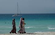 Tradtionally dressed Muslim girls walk along Nungwi beach..Nungwi Beach, Zanzibar, Africa.© Demelza Cloke