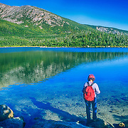 Hiker by a pond on Mount Katahdin. Maine
