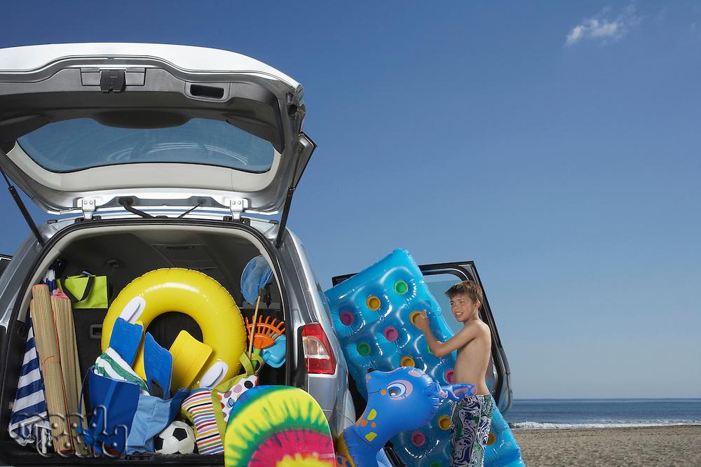Boy (10-12) unloading air mattress from car full of beach accessories