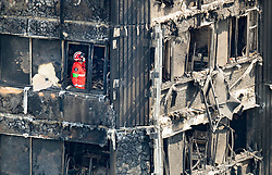 © Licensed to London News Pictures. 18/06/2017. London, UK. A member of London Fire Brigade's Urban Search and Rescue Team works on the 11th floor of the fire ravaged Grenfell tower block. The blaze engulfed the 27-storey building killing dozens - with 34 people still in hospital, many of whom are in critical condition. The fire brigade say that they don't expect to find anyone else alive. Photo credit: Peter Macdiarmid/LNP