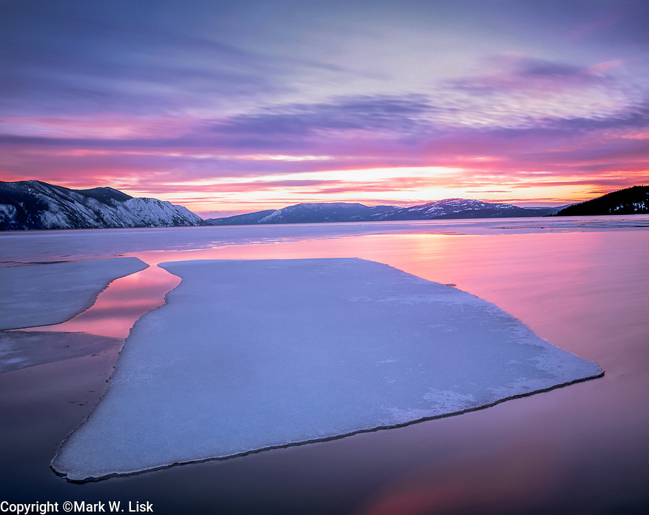 Ice thaws at Lake Pend Oreille in the soft light of a pastel sunset.