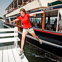 A girl jumps off the mailboat that delivers mail to residents on Lake Geneva in Wisconsin during the summer