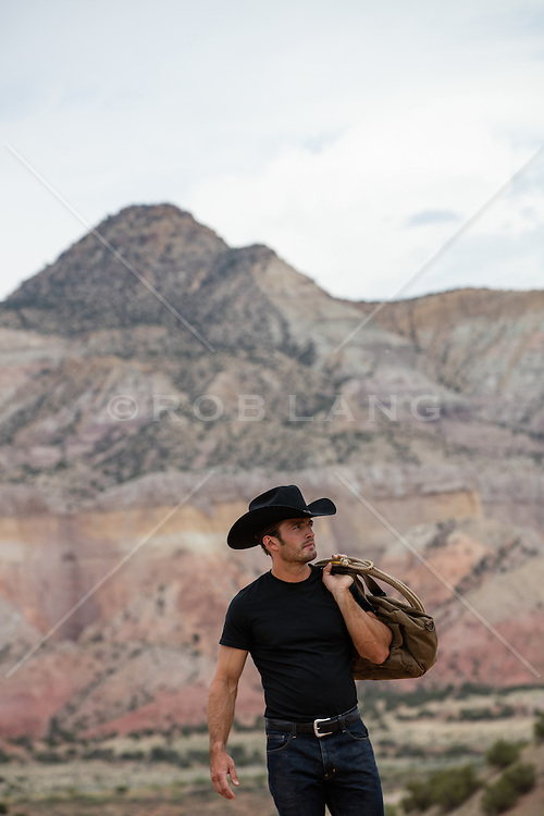 cowboy holding a lasso and duffle bag outdoors by a mountain range