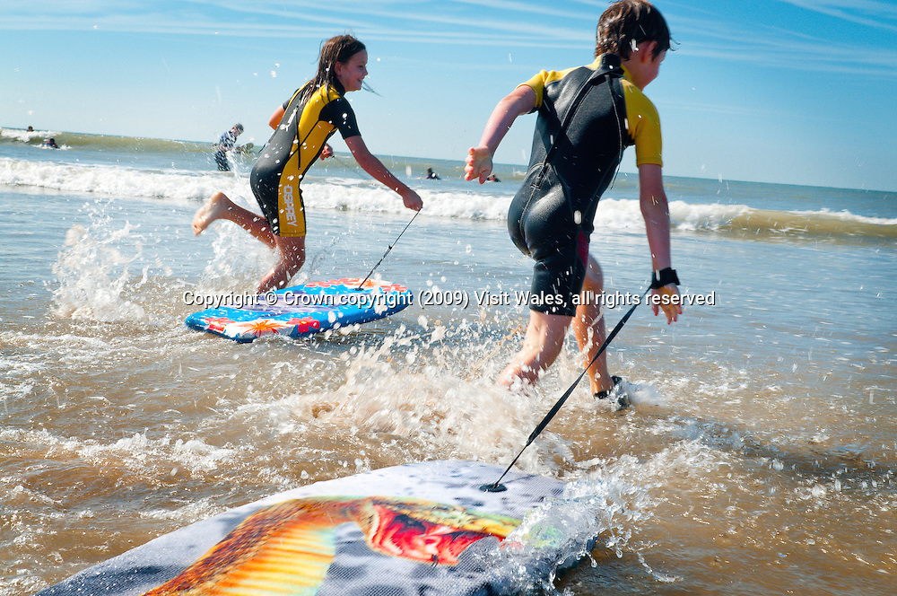 Children body-boarding<br /> Rest Bay beach<br /> Porthcawl<br /> Vale Of Glamorgan<br /> South<br /> Surfing<br /> Activities &amp; Sports