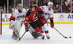Oct 10; Newark, NJ, USA; New Jersey Devils right wing David Clarkson (23) battles with Carolina Hurricanes goalie Cam Ward (30) and Carolina Hurricanes defenseman Jay Harrison (44) during the second period at the Prudential Center.