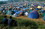 Two people sitting on the grass looking across a sea of tents, Glastonbury Festival, UK, 2000's