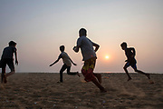 Four boys playing soccer on a beach in Bekal, Kerala, India.