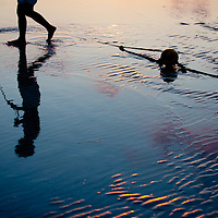 A woman walks her dog as the sun sets at St. Pete Beach.