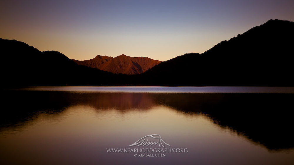 The first light of the morning casts its favor on the mountain range behind the lake, while the mountain range adjacent to Green Lake continues to slumber.