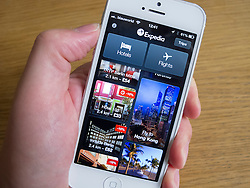 Using Expedia app to book travel on white iPhone 5 smartphone