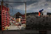 EIn Maurer an der Arbeit. Neubau im Greyerz, La Tour-de-Trême, Juni 2010. Maçon à l'ouvrage, ciment et briques