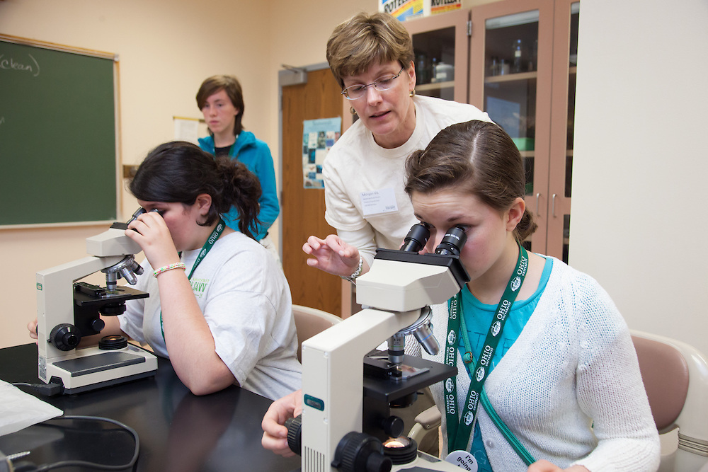 Instructor Morgan Vis explains to Rachael Puls how to use a microscope to check for water quality during the Tech Savvy workshop at Ohio University May 17, 2014.  The full day event exposes girls from sixth through ninth grade to the field of science, technology, engineering and math.    Photo by Ohio University / Jonathan Adams