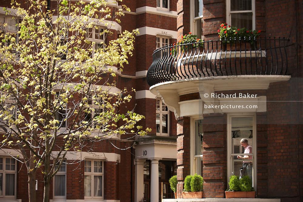 Window cleaner stands on ledge of handsome red brick Victorian properties in D'Oyley Street, London's Belgravia, SW1