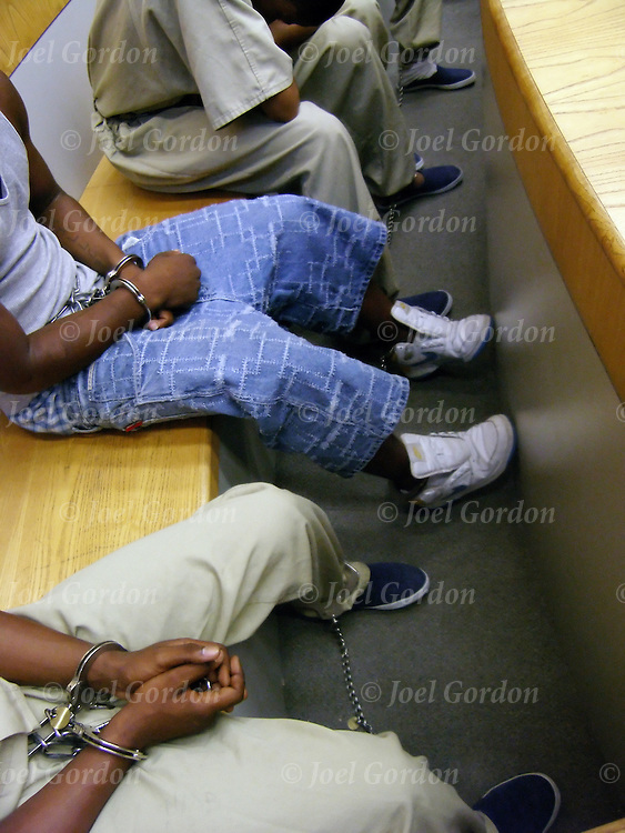 Preliminary Hearning - ?Jail Call? docket in Juvenile Court, teens handcuffed waiting before court for their cases to be heard by judge. Some are wearing jail jump suits while other are wearing street cloths and handcuffs