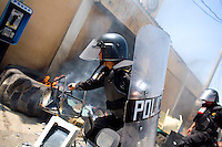 A special anti riot police officer tries to pull burning debris away from the mayors office after protestors set it on fire Tuesday Sept. 11, 2007, Palin Guatemala. A angry mob took to the streets and went on to burn down the mayors office as well as his home in demonstration after and clash with local police on the previous day. Residents accuse the mayor of, among other things, of bussing voters for the elections on Sept. 9 2007.   (photo by/ Darren Hauck).................