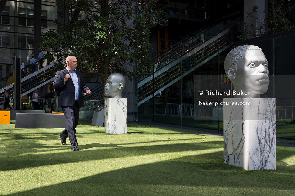 An office worker walks past sculpture outside the Leadenhall Building during the 2018 heatwave in the City of London, the capital's financial district, on 24th July 2018, in London, England.