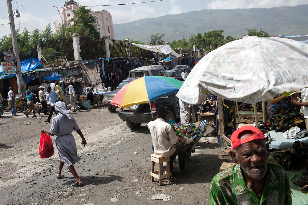 A busy streetcorner comes to life as the ruins of the cathedral loom in the background on July 8, 2010 in Port-au-Prince, Haiti.