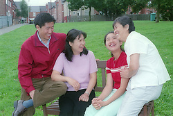Family sitting on a bench in the park laughing,