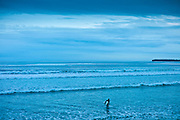 Lone surfer leaving the surf at high tide at beach resort of Lahinch (Lehinch) at twilight, County Clare, West Coast of Ireland