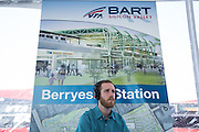 An audio technician listens to speeches in front of BART Berryessa Station signage during VTA's BART Silicon Valley Extension Celebration in San Jose, California, on August 20, 2014. (Stan Olszewski/SOSKIphoto)