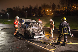 © Licensed to London News Pictures . 05/11/2015 . Salford , UK . Fire crews damp down a burned out Transit van on Graythorpe Walk . Manchester Fire reports receiving more than 300 calls in less than 7 hours, from 4.30pm, including to buildings, cars and wheelie bins set alight by arsonists . At some calls fire crews were subject to vandalism , including a hose being sliced whilst it was being used to fight a fire in Leigh and bricks being thrown at crews attending a job in Miles Platting . Fire crews deal with arson attacks across Greater Manchester during Bonfire Night . Photo credit : Joel Goodman/LNP