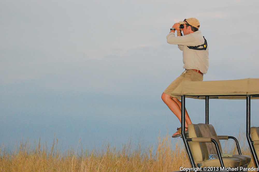 A safari guide scans the horizon for wildlife near sunset, Gorongosa National Park, Mozambique