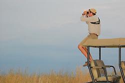 A safari guide scans the horizon for wildlife near sunset, Gorongosa National Park, Mozambique