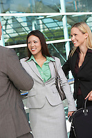 Businesswomen shaking hands with businessman outside office building