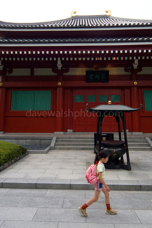Girl passes shrine at Asakusa Kannan Temple Gardens Tokyo, Japan
