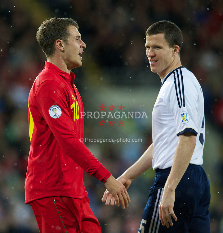 CARDIFF, WALES - Friday, October 12, 2012: Wales' Aaron Ramsey and Scotland's Gary Caldwell exchange words during the Brazil 2014 FIFA World Cup Qualifying Group A match at the Cardiff City Stadium. (Pic by David Rawcliffe/Propaganda)