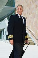 Airline pilot pulling suitcase outside building, portrait