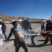 'Attitude at Altitude' Football in Potosi, Bolivia'..Players and fans from Calvario celebrate their win over Galpes S.C. teams during the Liga Deportiva San Cristobal cup final on the stone and gravel surface high in the hills over Potosi, Calvario won the match 3-1. Potosi, Bolivia 9th May 2010..'Attitude at Altitude' Football in Potosi, Bolivia'..The Calvario players greet the final whistle with joyous celebration, high fives and bear hugs the players are sprayed with local Potosina beer after a monumental 3-1 victory over arch rivals Galpes S.C. in the Liga Deportiva San Cristobal. The Cup Final, high in the hills over Potosi. Bolivia, is a scene familiar to many small local football leagues around the world, only this time the game isn't played on grass but a rock hard earth pitch amongst gravel and boulders and white lines that are as straight as a witches nose, The hard surface resembles the earth from Cerro Rico the huge mountain that overlooks the town. .. Sitting at 4,090M (13,420 Feet) above sea level the small mining community of Potosi, Bolivia is one of the highest cities in the world by elevation and sits 'sky high' in the hills of the land locked nation. ..Overlooking the city is the infamous mountain, Cerro Rico (rich mountain), a mountain conceived to be made of silver ore. It was the major supplier of silver for the spanish empire and has been mined since 1546, according to records 45,000 tons of pure silver were mined from Cerro Rico between 1556 and 1783, 9000 tons of which went to the Spanish Monarchy. The mountain produced fabulous wealth and became one of the largest and wealthiest cities in Latin America. The Extraordinary riches of Potosi were featured in Maguel de Cervantes famous novel 'Don Quixote'. One theory holds that the mint mark of Potosi, the letters PTSI superimposed on one another is the origin of the dollar sign...Today mainly zinc, lead, tin and small quantities of silver are extracted from the mine by over 100 co operatives an