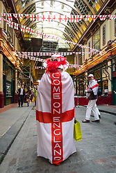 © Licensed to London News Pictures. 21/04/2017. LONDON, UK. A woman with an England coat leaves after watching Morris dancers perform in Leadenhall Market in the City of London today, ahead of the official St George's Day this Sunday. Photo credit: Vickie Flores/LNP