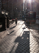 A pedestrian walks along Central Park South.  Long shadows are cast in the early morning winter light.