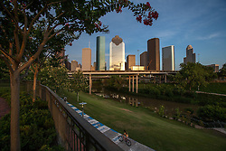 Houston, Texas skyline from Buffalo Bayou with people bicycling along path.