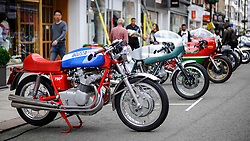 © Licensed to London News Pictures. 17/06/2018. LONDON, UK. Visitors view (L to R) an MV Agusta 750S motorcycle, a Ducati 750 SS 1974 motorcycle and a Ducati 900 Mike Hailwood Replica motorcycle at the 6th Annual Classic and Supercar Pageant held at St John's Wood High Street.  Traditionally taking place on Fathers' Day, the show brings together an eclectic mix of exotic and popular vehicles attracting visitors young and old and raises funds for the local charity, The St John's Hospice.  Photo credit: Stephen Chung/LNP