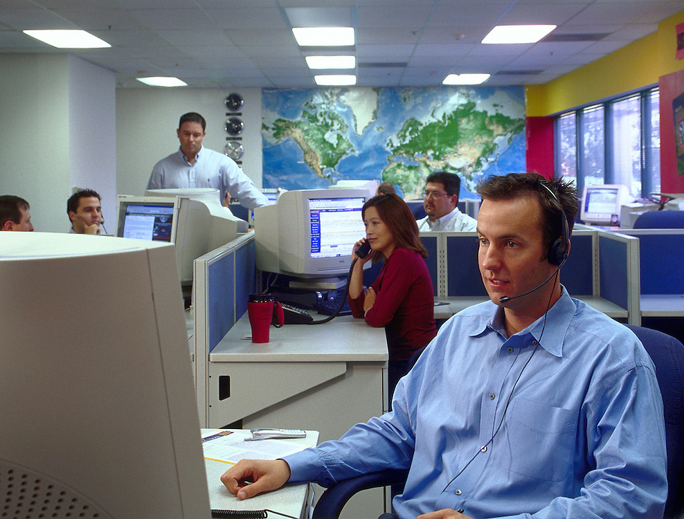 Telemarketing office with workers on phones and computers.