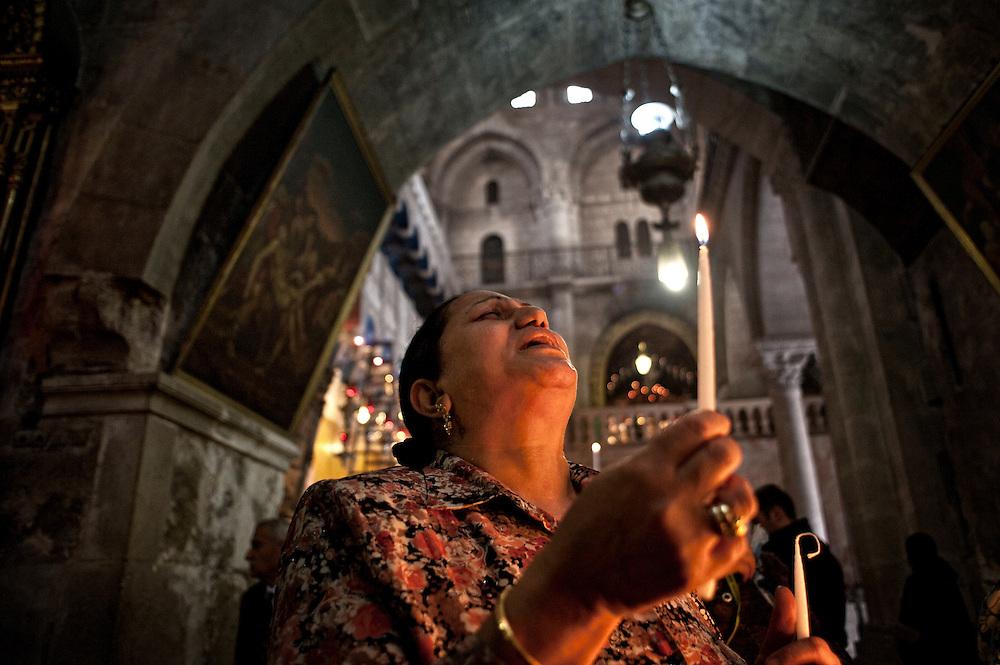 Jérusalem, israël, le 17 avril 2011 - Début des festivités de la semaine sainte. Une femme prie un cierge à la main en l'église du Saint Sépulcre.
