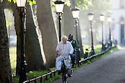 Een man fietst met tassen aan het stuur over de Van Asch Van Wijckkade in Utrecht.<br /> <br /> A man is cycling in Utrecht.