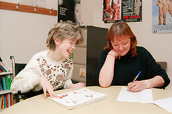 Teacher and girl with learning difficulties; who is wheelchair user; sitting at desk in classroom laughing,