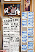 "A photo of former Japan Prime Minister Yukio Hatoyama hangs above  the business registration certificate and employee time card holder of Harumiya Co.'s ""Yakata-bune"" pleasure boat business in Tokyo, Japan on 31 August  2010. Photographer: Robert Gilhooly"