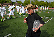 7 MAY 2009 -- CREVE COEUR, Mo. -- The Rev. Michael Marchlewski, known to generations of students at St. Louis University High School and DeSmet Jesuit High School as Father Marco, carries to midfield the cup that is award to the winner of the annual game between the schools' lacrosse teams following the 7th annual Father Marco Cup at DeSmet Saturday, May 8, 2011. The Rev. Marchlewski spent the first half on the DeSmet sidelines and the second half on the SLUH bench. Image © copyright 2011 Sid Hastings.