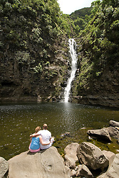 Hawaii: Molokai, Halawa Valley, couple at waterfalls, end of hike in past taro fields, ancient walls, to waterfalls, guided by Lawrence Aki.  Model released. .Photo himolo236-72417..Photo copyright Lee Foster, www.fostertravel.com, lee@fostertravel.com, 510-549-2202