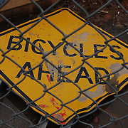 """Bicycles Ahead"" road sign on ground behind chain link fence during Tucson's Interstate 10 widening project. Bike-tography by Martha Retallick."